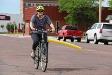 Katie Bradshaw bikes with pool noodle